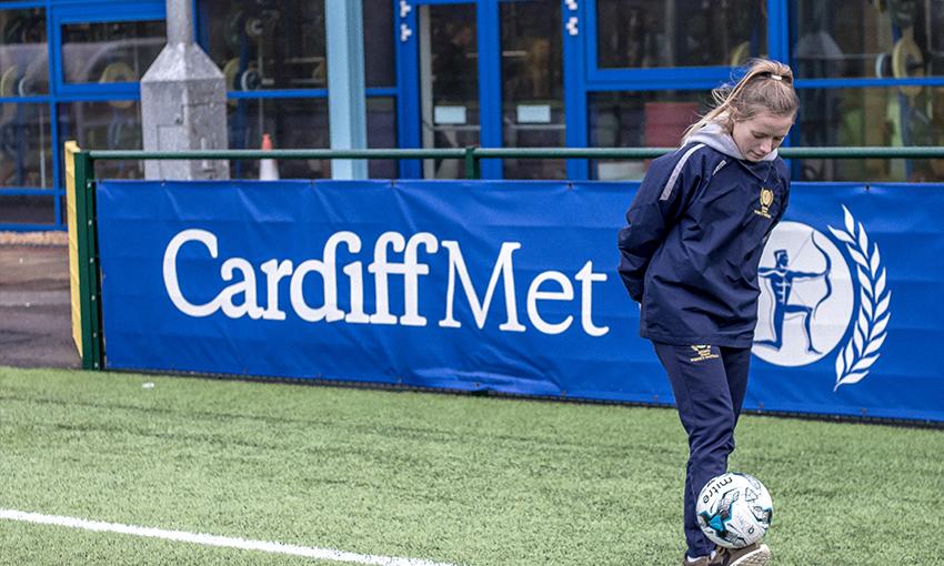 A young woman kicks a football