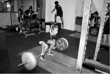 A young woman deadlifts in the gym