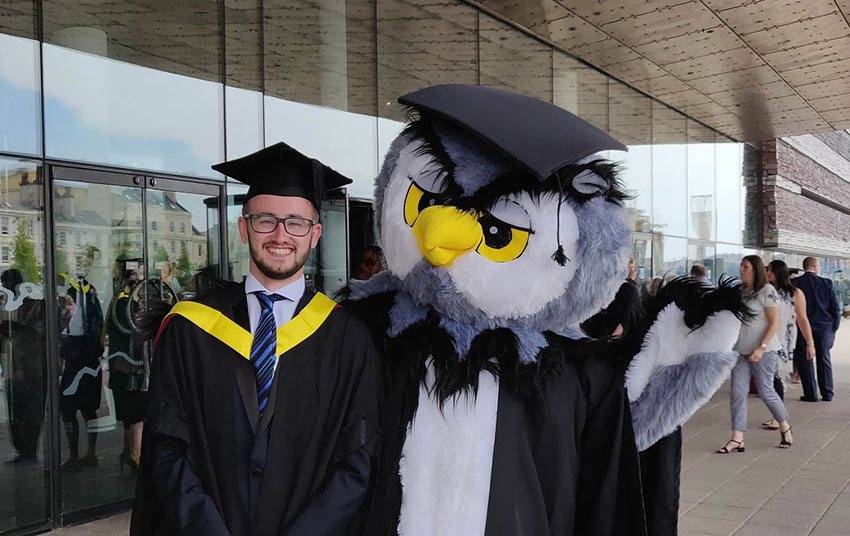 Tom at graduation with the Edwin the owl mascot
