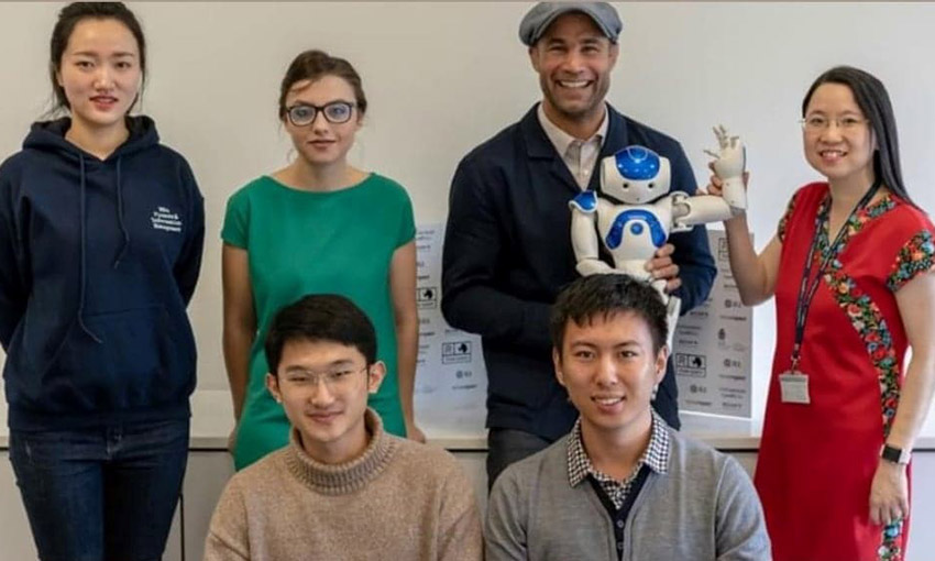 Eliza and her course mates with Dr Esyin Chew and Richard Parks who is holding a NAO Robot