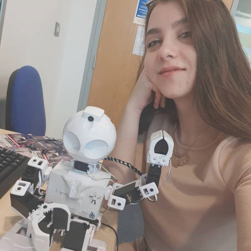Eliza smiling with a JD robot