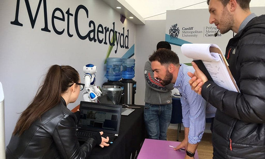 Eliza talking to two reporters whilst working on her laptop with the robot