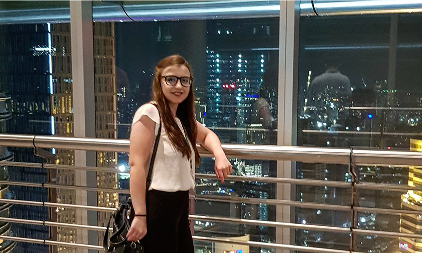 Eliza Georgescu in front of a window with a view from the top of the Petronas Towers