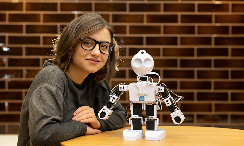 Eliza Georgescu smiling with JD robot