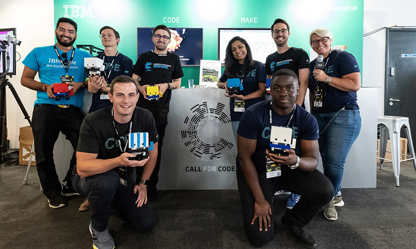 Cameron and seven other colleagues posing in front of the IBM stand at the FullStack conference