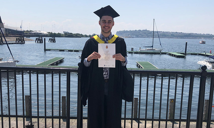 Joel poses with his degree certificate in front of the sea at Cardiff Bay