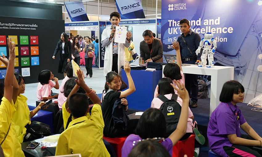 Lots of kids sat in front of the UK booth with their hands raised while a member of the team talks on the microphone