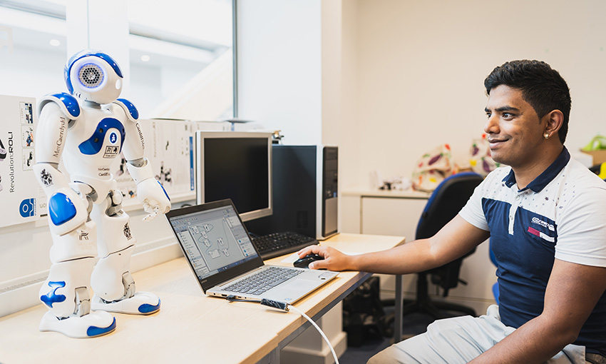 Pawr sitting at a desk with a laptop and the NAO robot, looking at each other