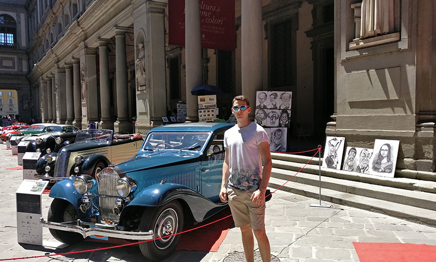 Josh standing in front of old cars in Florence