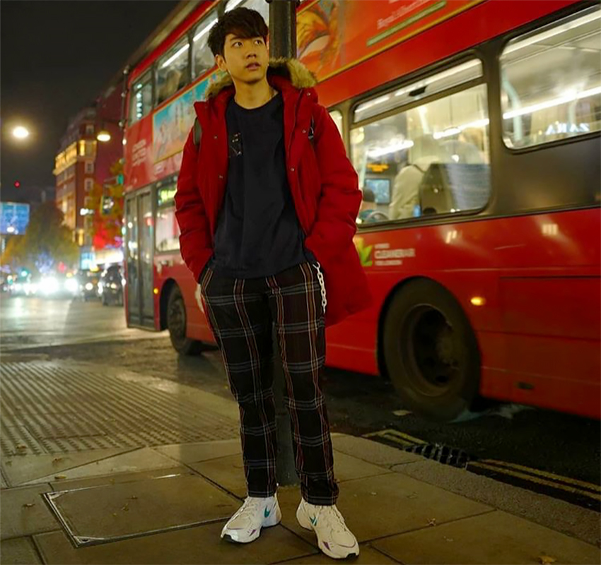 Tora stands in front of a red bus