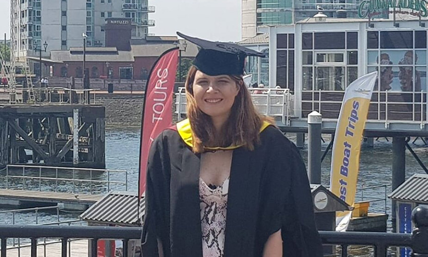 Sarah wearing her cap and gown in Cardiff Bay on her graduation day