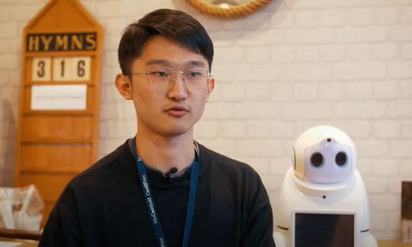 Jaiji Yang with a robot